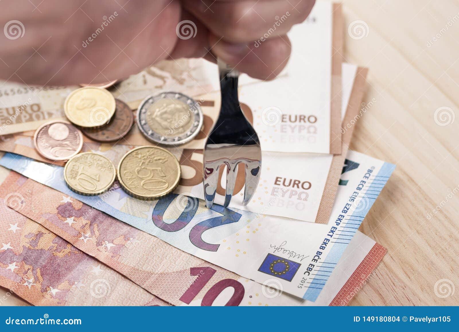 Une main avec une fourchette métallique brillante bat une pile des billets de banque et des pièces de monnaie d euro