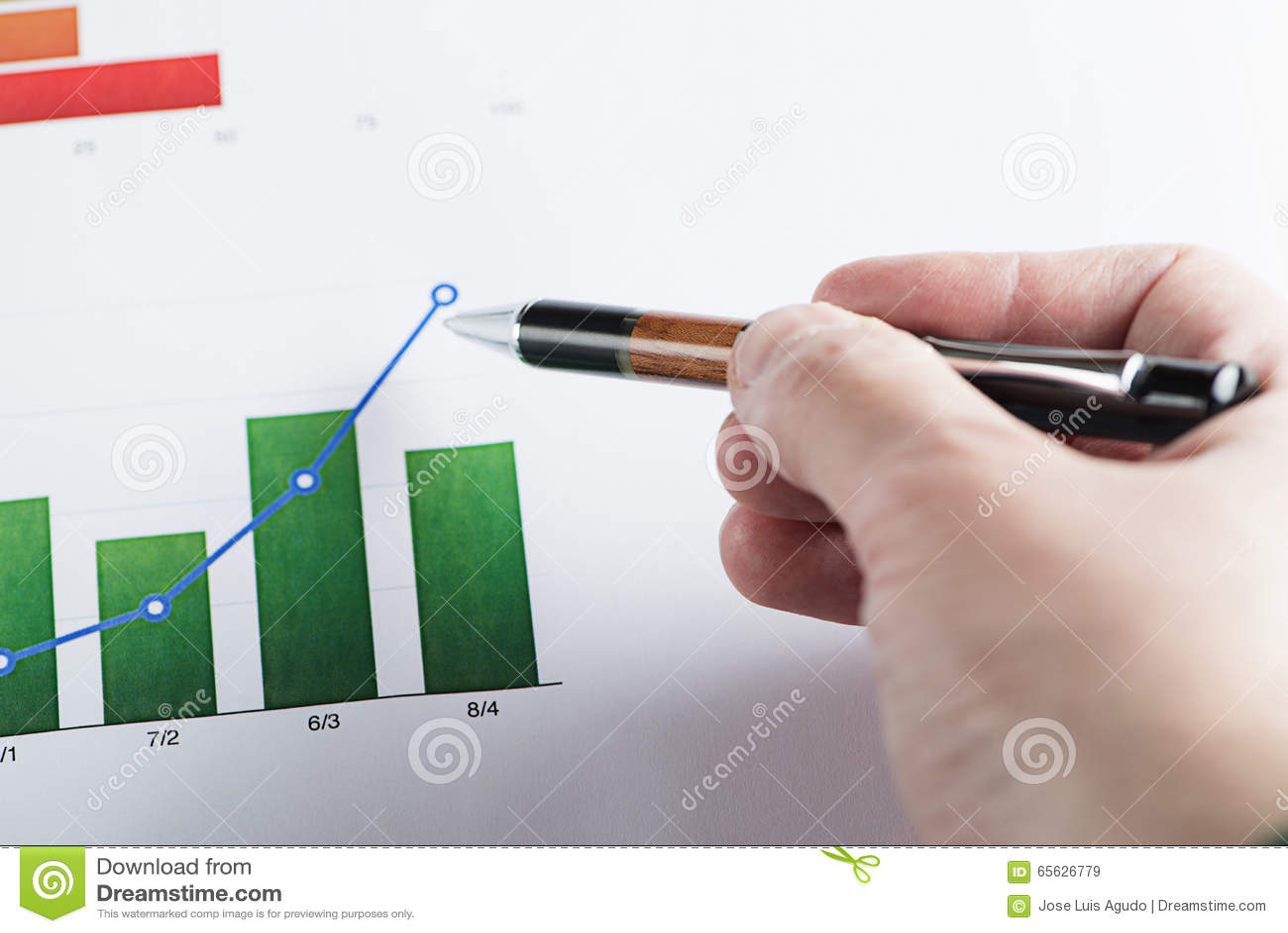 Une main avec un stylo se dirigeant sur les graphiques colorés de finances