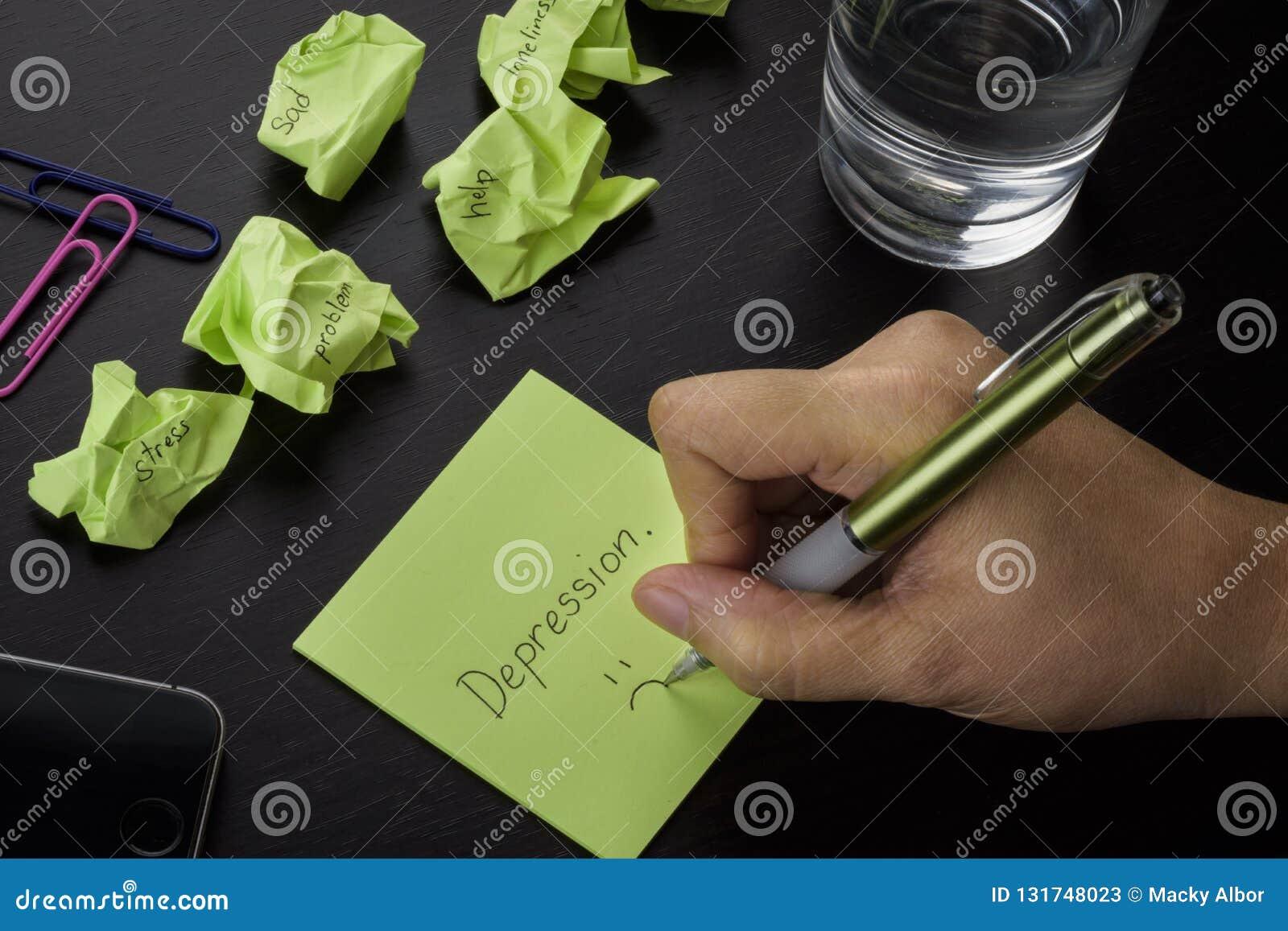 """Une main dépression écrivant sur une note collante verte mot """" """"Une photo au sujet de dépression, de tristesse et de solitude Sti"""