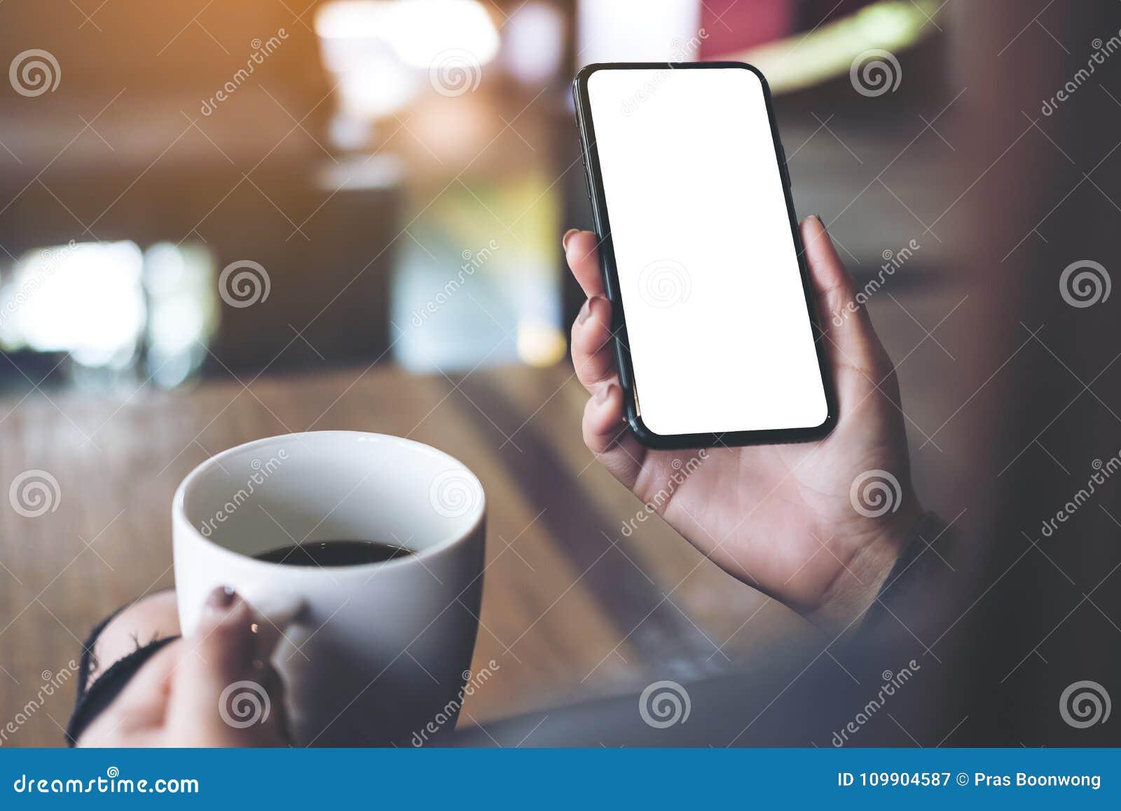 Une main du ` s de femme tenant le téléphone portable noir avec l