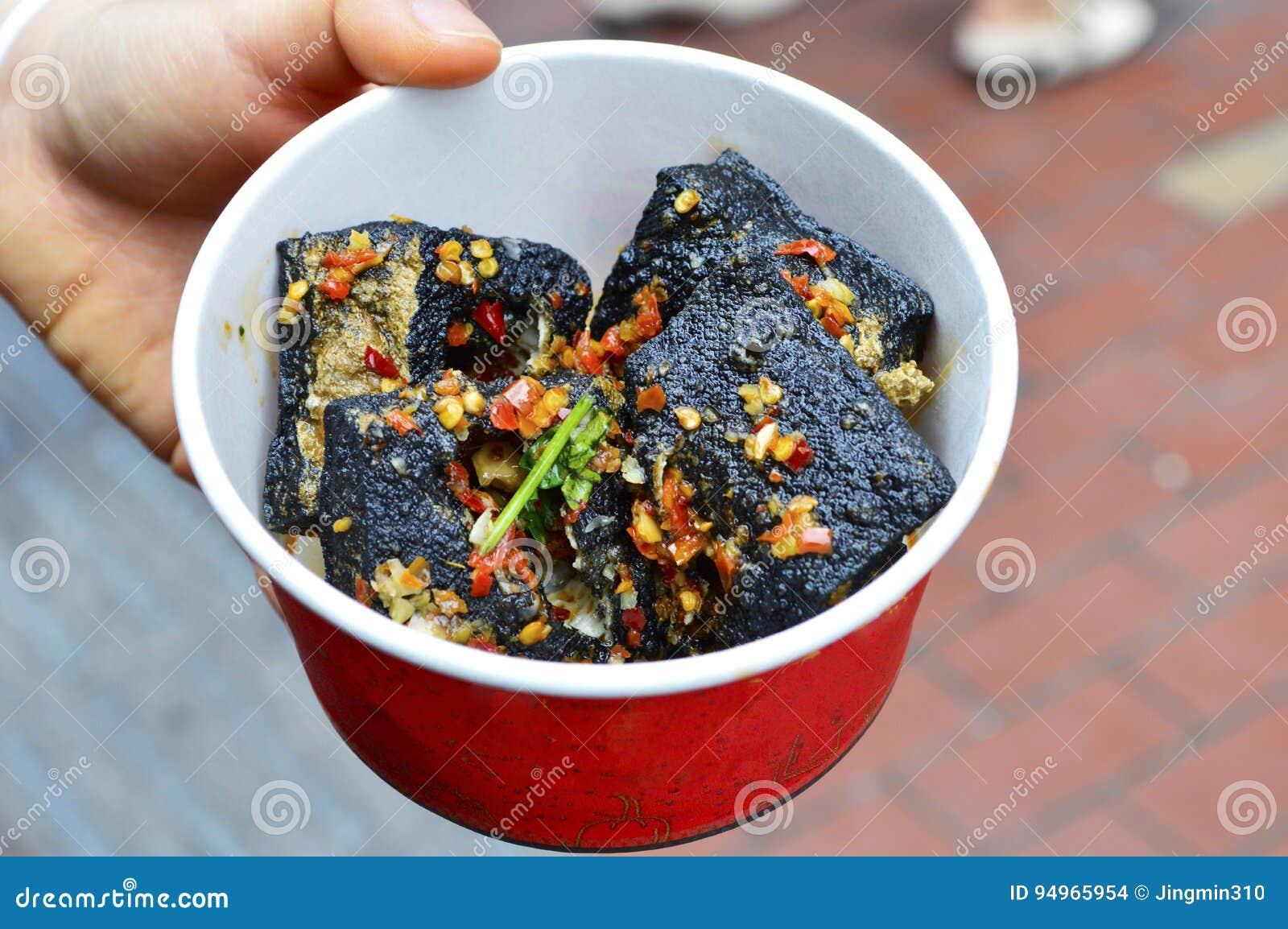 Une main Hoiding une boîte avec Fried Stinky Tofu profond noir