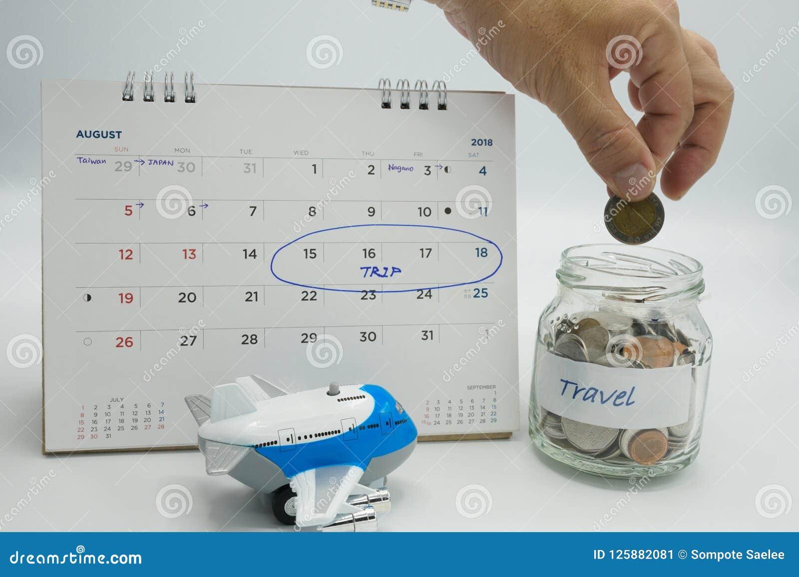 Une main mettant une pièce de monnaie dans un pot en verre rempli de pièces de monnaie marquées voyagent