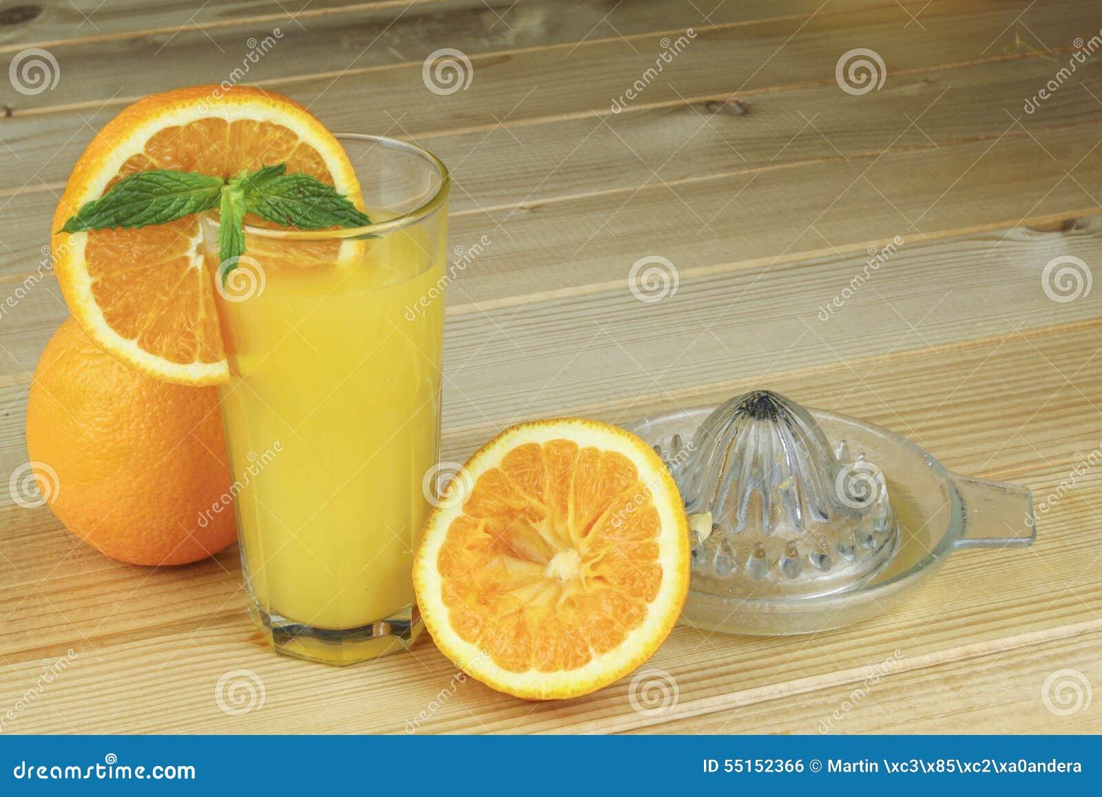 Une main serrant le jus d une orange sur un presse-fruits en verre manuel Placez sur une table planked en bois