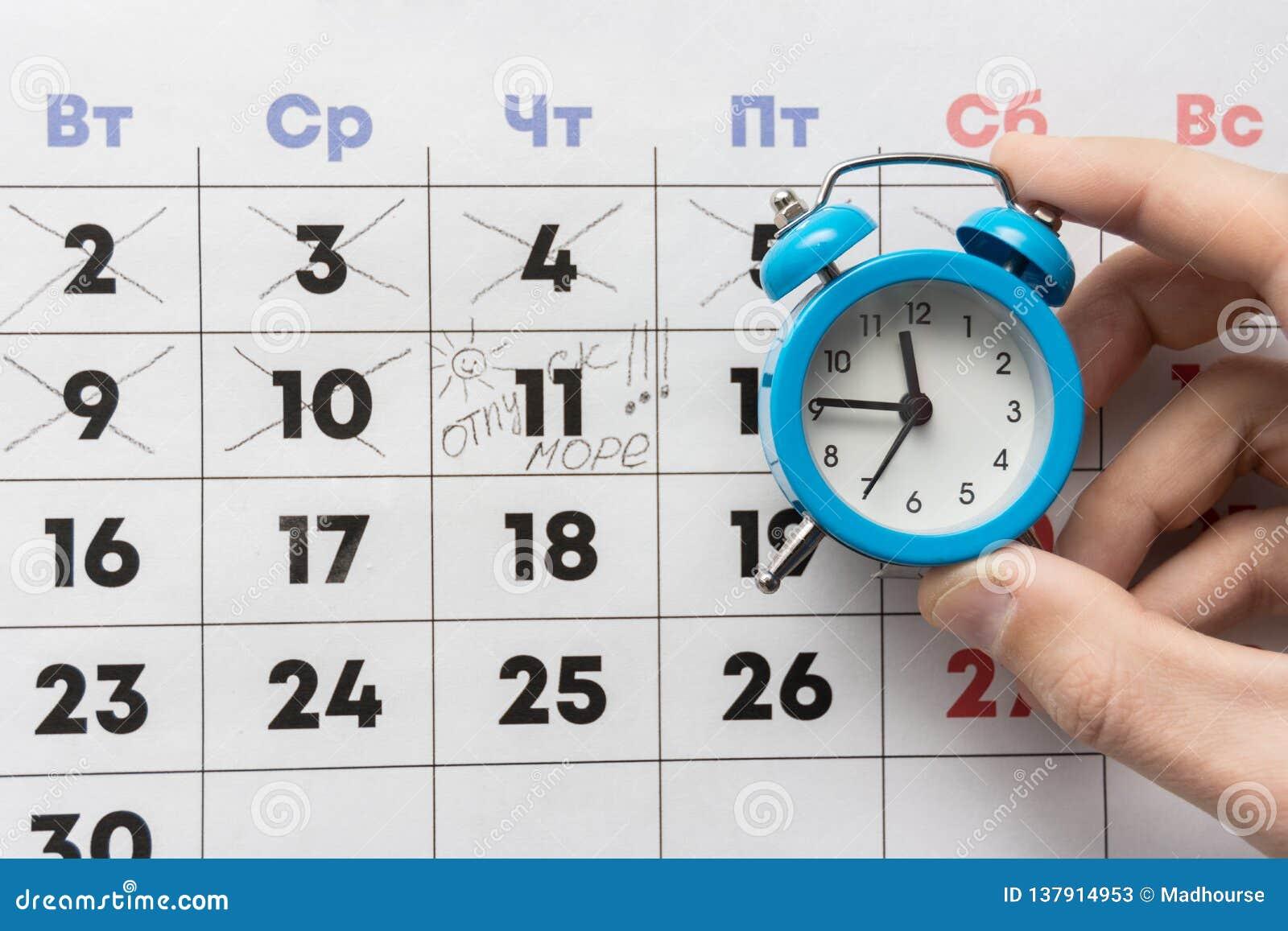 Une main tient un petit réveil, à l arrière-plan est un calendrier avec le jour marqué et les vacances de mot