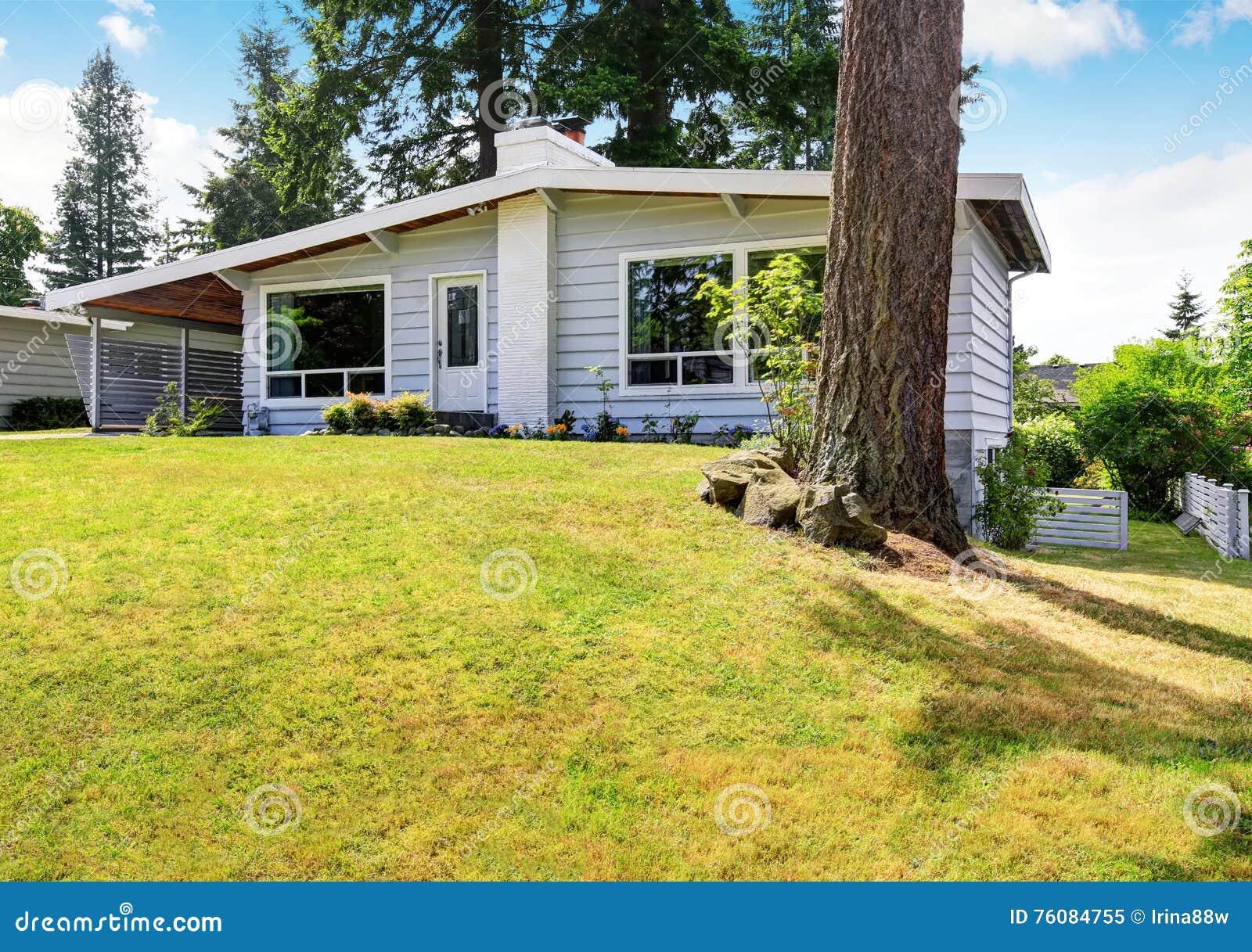 Une maison de niveau avec l équilibre de voie de garage et la pelouse soignée