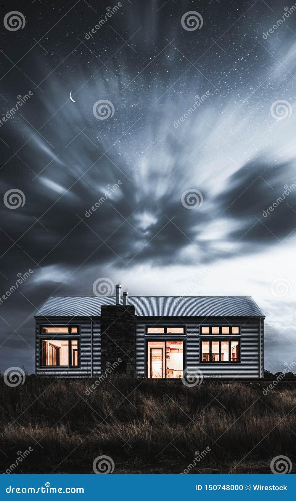 Une maison mystérieuse avec les lumières dessus dans un domaine foncé
