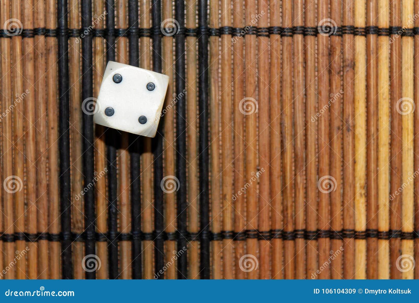 Une matrice en plastique blanche sur le fond brun de conseil en bois Six cubes en côtés avec les points noirs Numéro 4