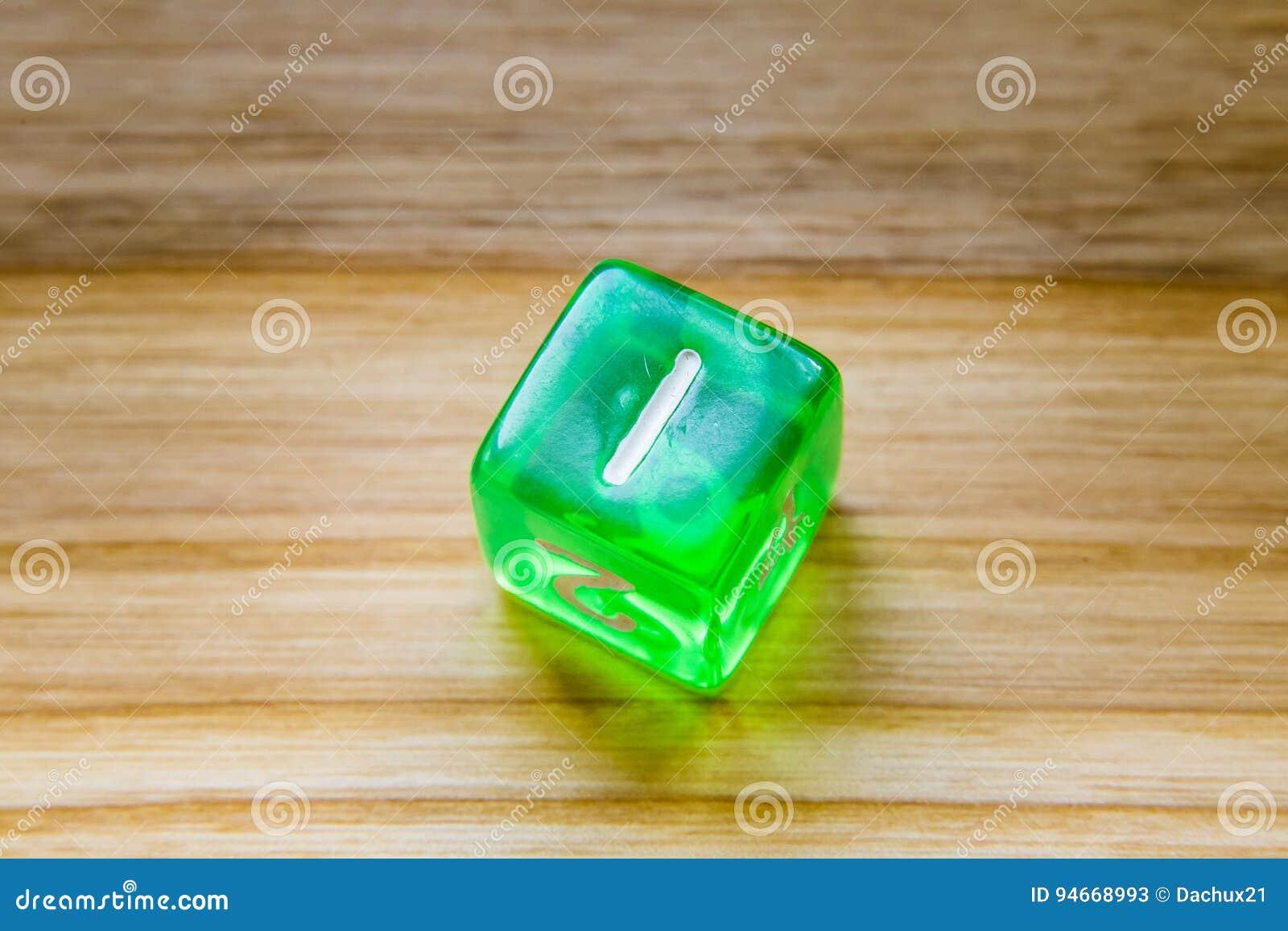 Une matrice jouante hexagone verte translucide sur un backgroun en bois