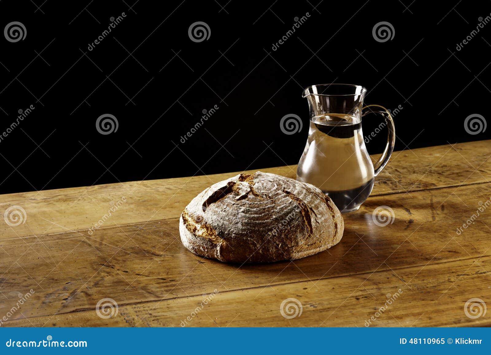 une miche de pain et une cruche de l 39 eau sur la table en bois photo stock image 48110965. Black Bedroom Furniture Sets. Home Design Ideas