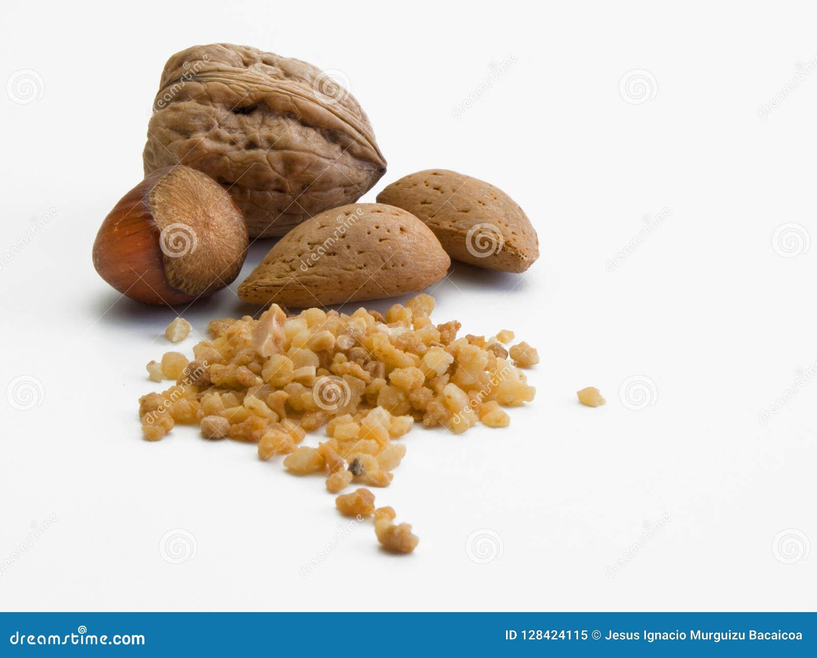 Une noix, deux amandes et une noisette ainsi qu une petite pile des mêmes fruits