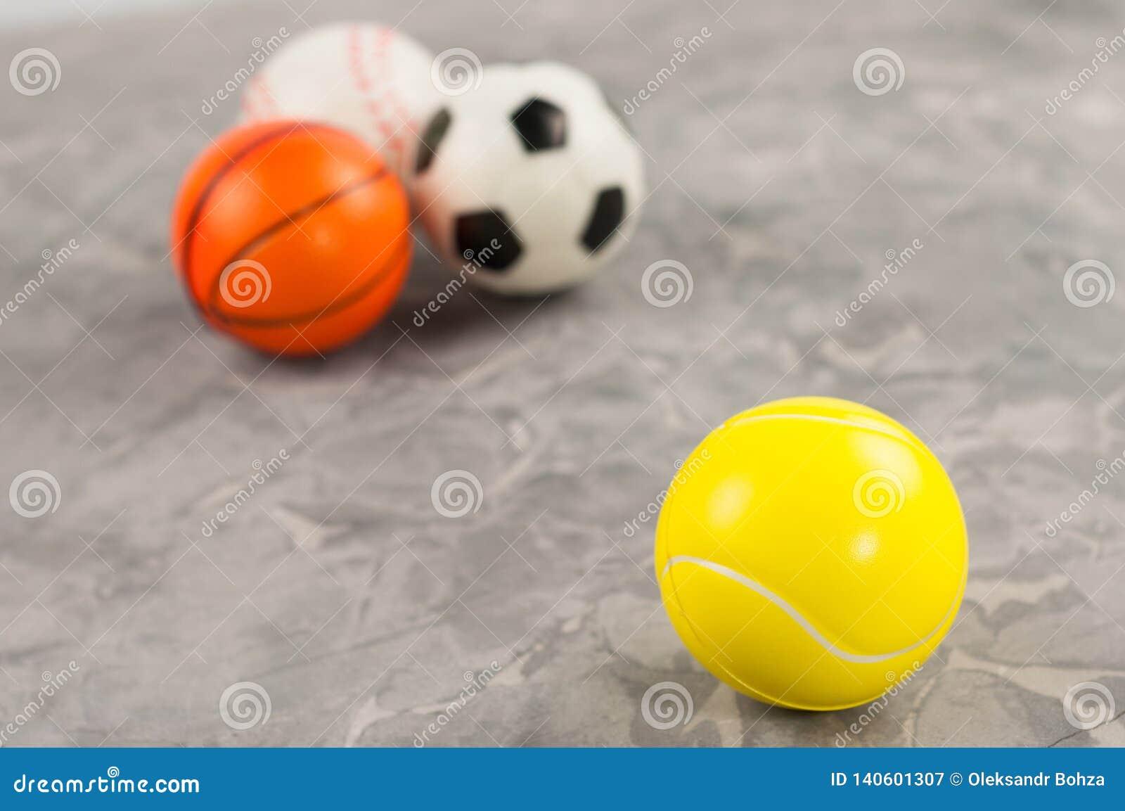 Une nouvelle balle de tennis molle en caoutchouc sur le fond de trois boules différentes de sports