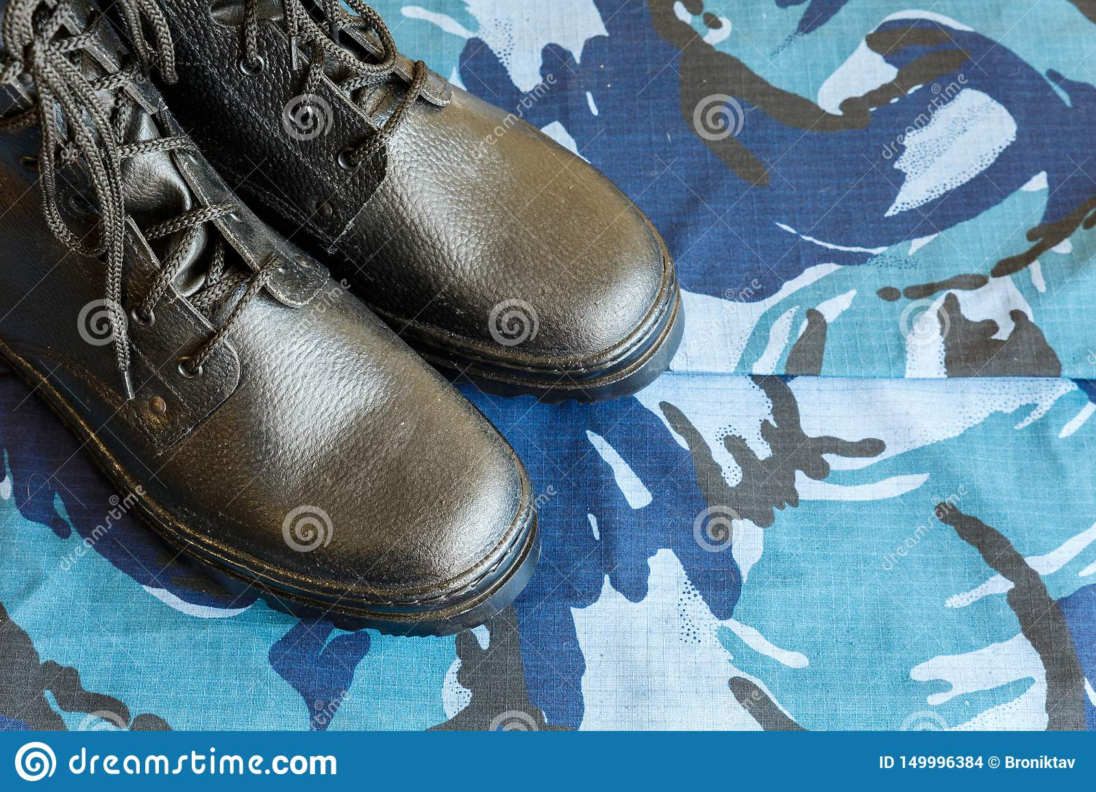 Une paire de bottes noires d armée sur le tissu avec le camouflage bleu avec le copispace pour le texte