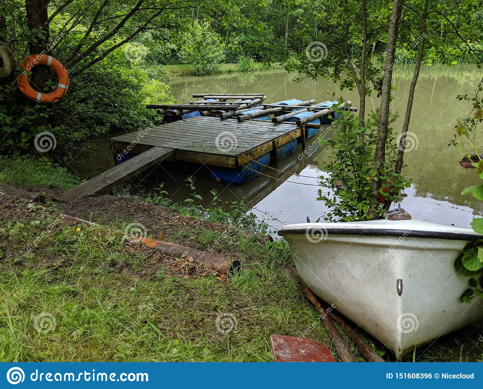 Une paire de radeaux sur un ponton avec un petit bateau à rames sur la banque de rivage