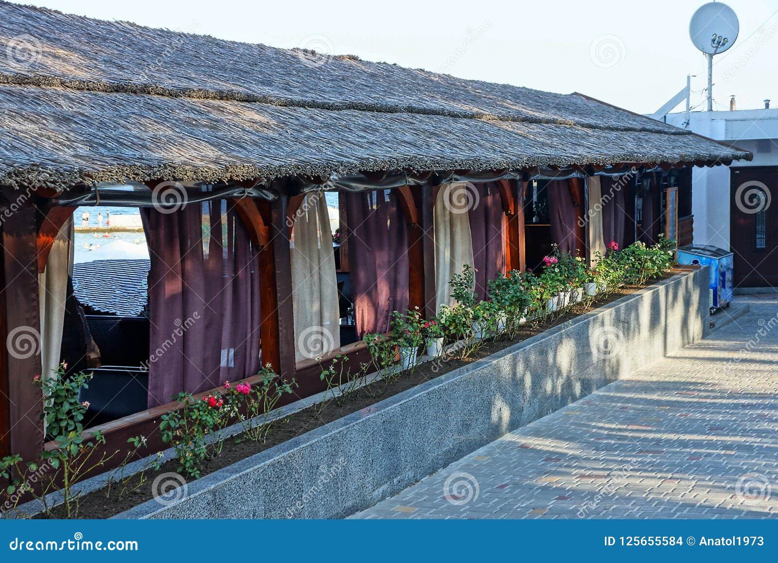 Une partie d une longue terrasse brune sous un toit couvert de chaume avec des rideaux et des pots de fleurs avec des fleurs