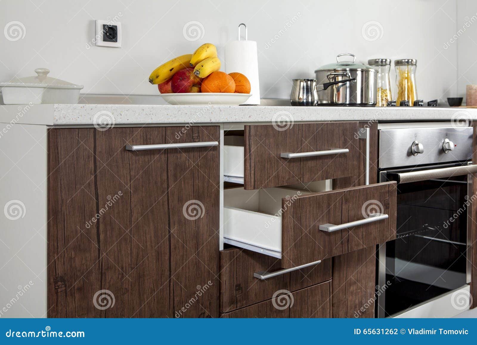 Une partie de cuisine moderne avec le four électrique de fourneau, tiroirs, poignée