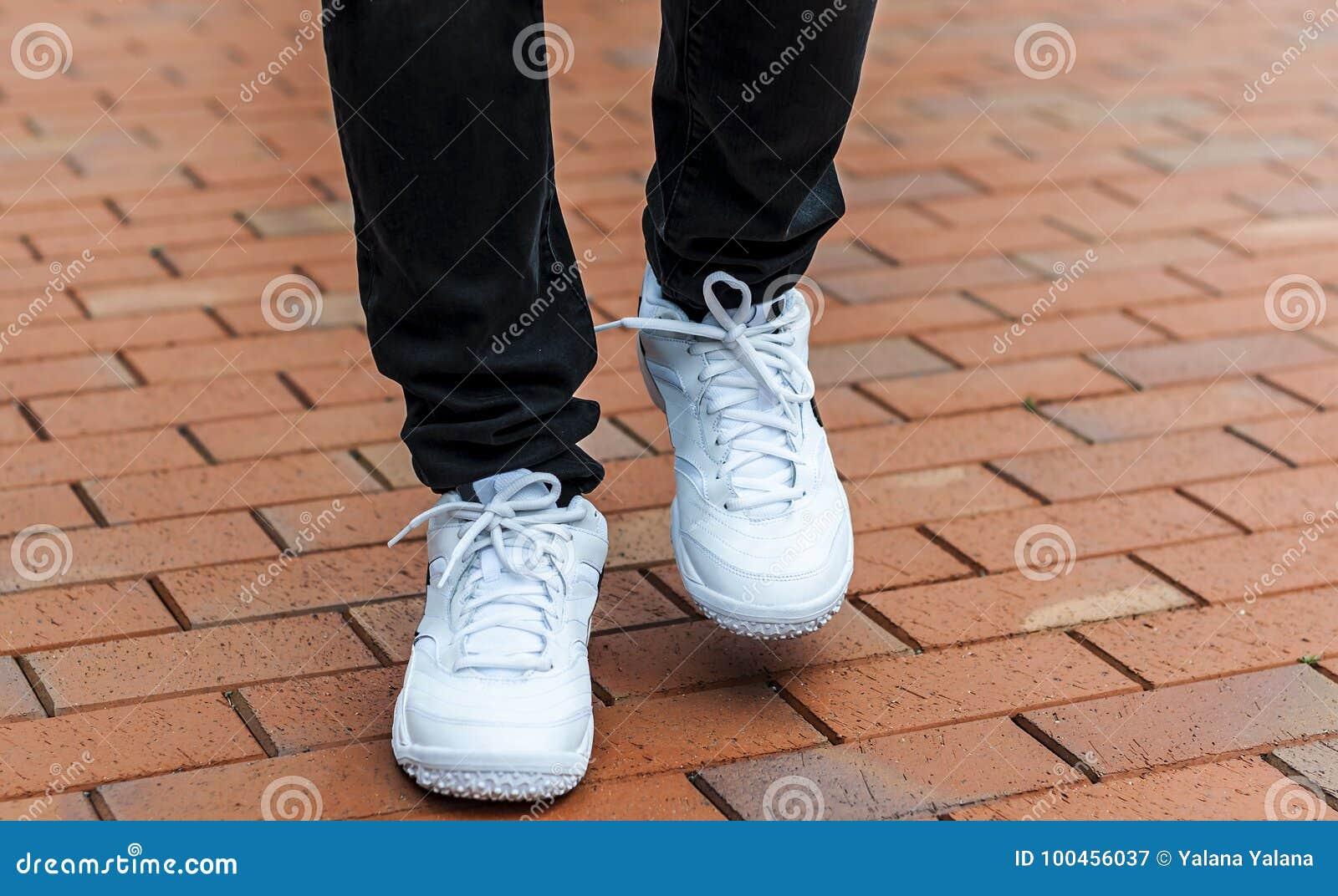 Une partie plus inférieure des jambes masculines dans des espadrilles blanches