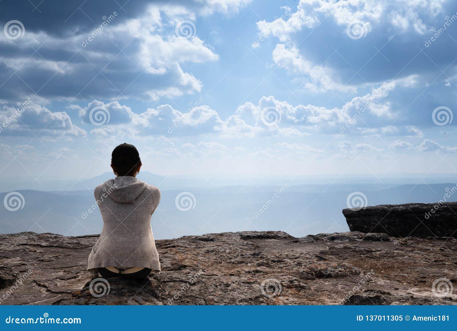 Une personne s asseyant sur la montagne rocheuse regardant la vue naturelle scénique