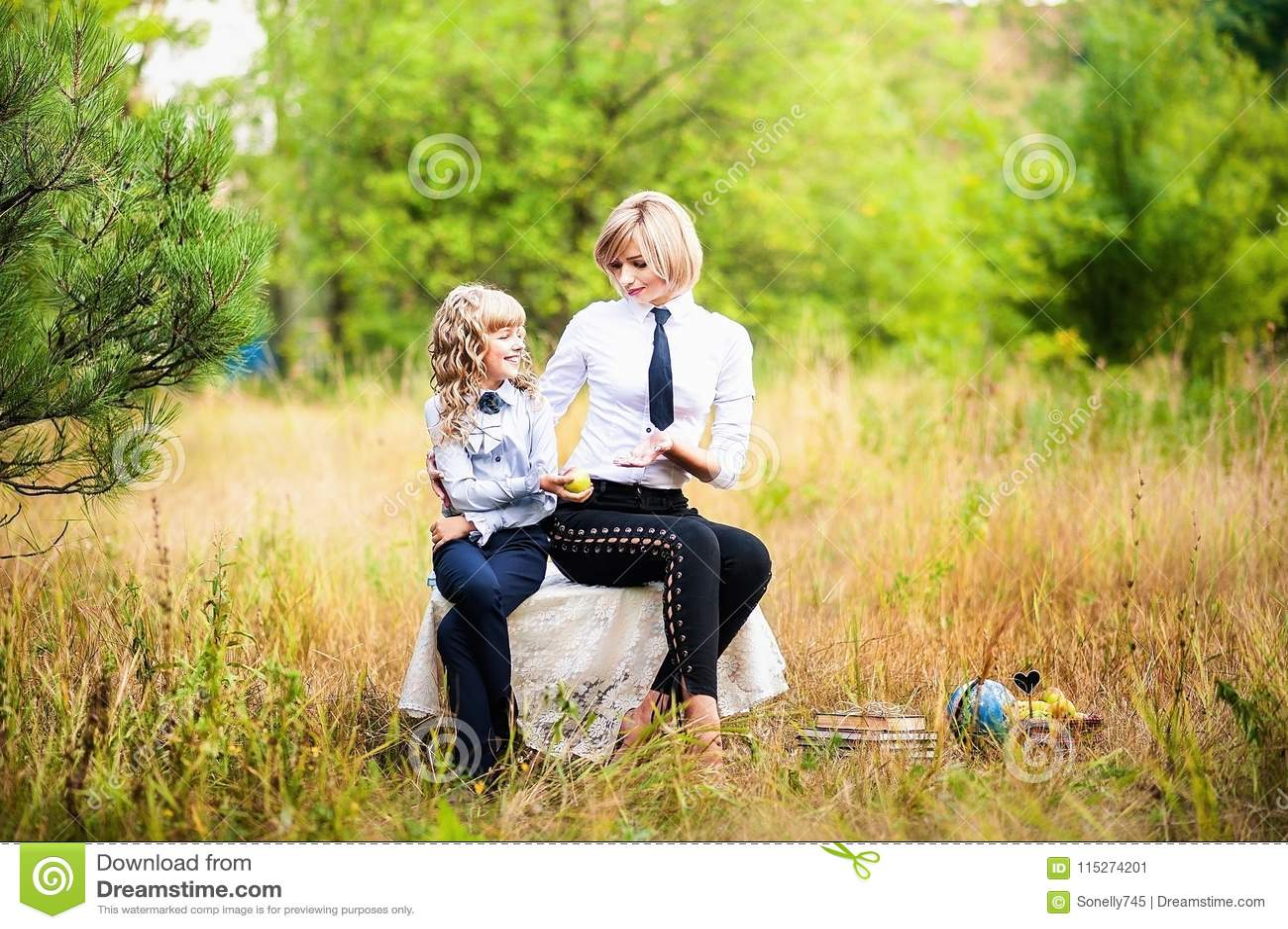 Une petite écolière et un diplômé adulte dans l uniforme scolaire tiennent une pomme contre le contexte d une forêt verte