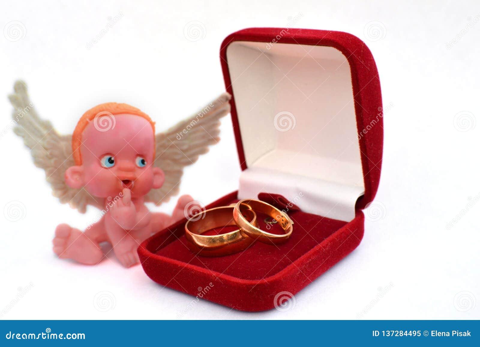Une petite figure d un ange se reposant près d une boîte à bijoux avec deux anneaux les épousant d or d isolement sur le blanc