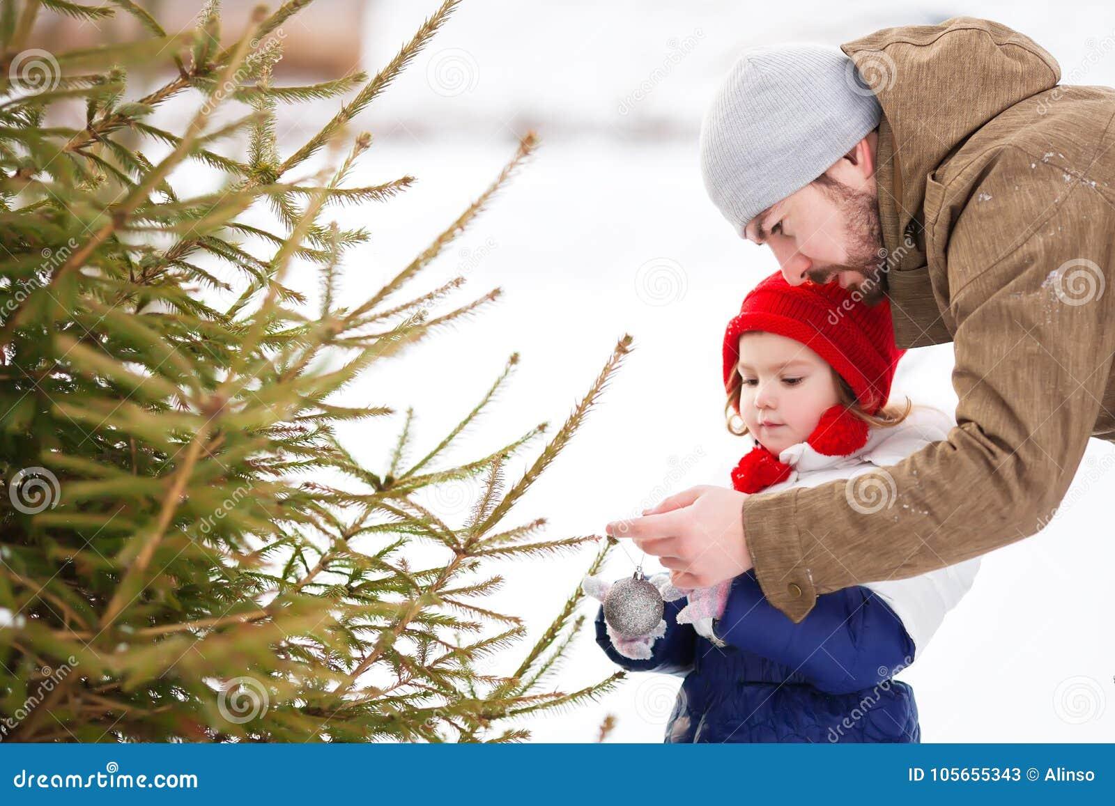 Une petite fille aide son père à décorer un arbre de Noël dehors