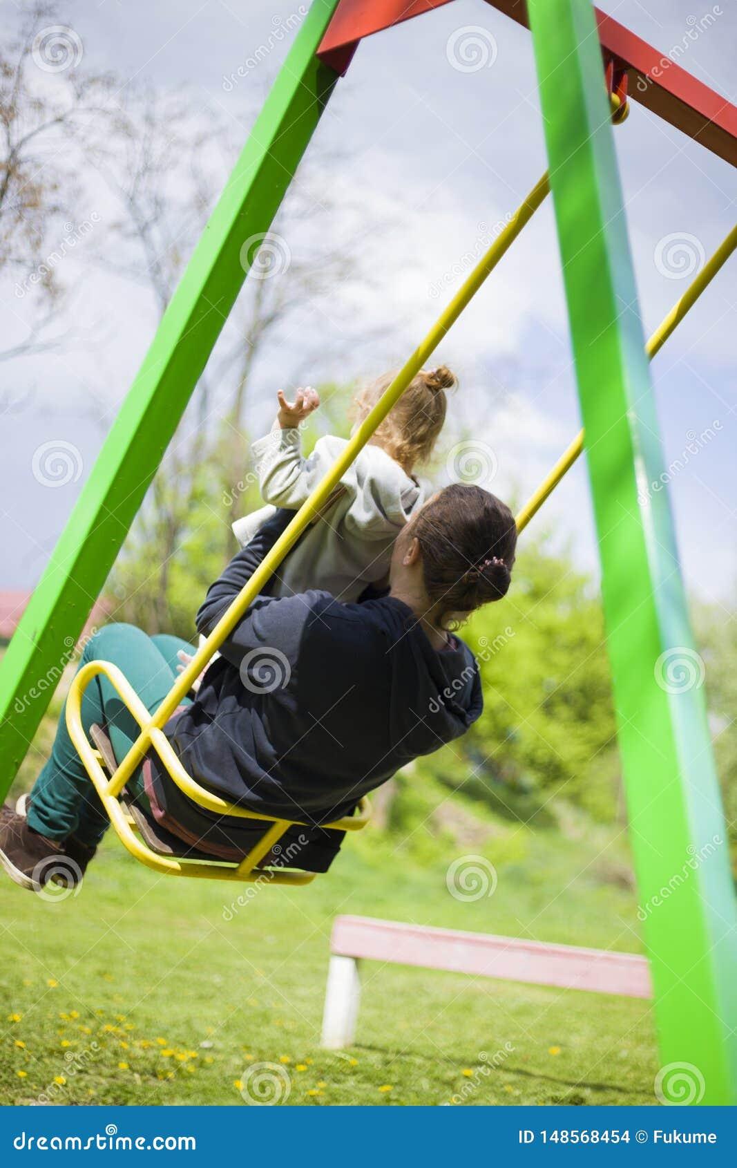 Une petite fille avec sa m?re dans le tour de parc sur une oscillation et avoir un bon week-end concept d un enfant heureux d enf