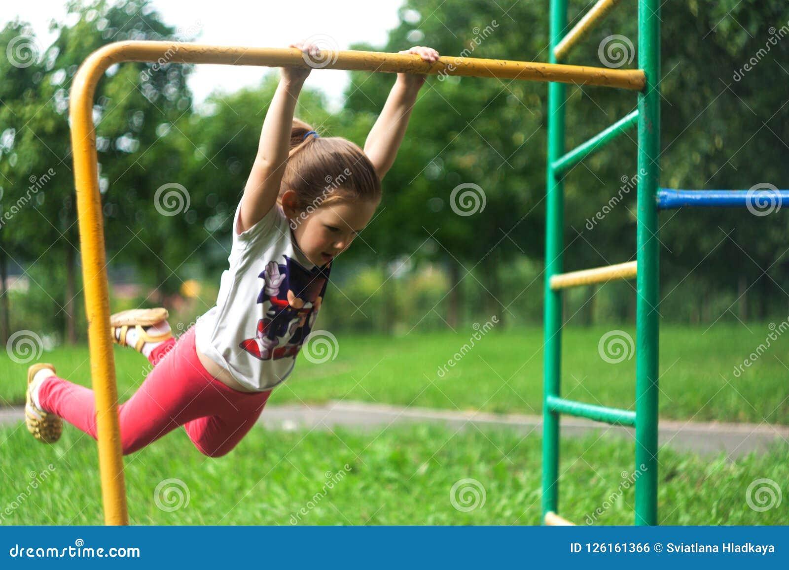 Une petite fille balance sur une barre transversale