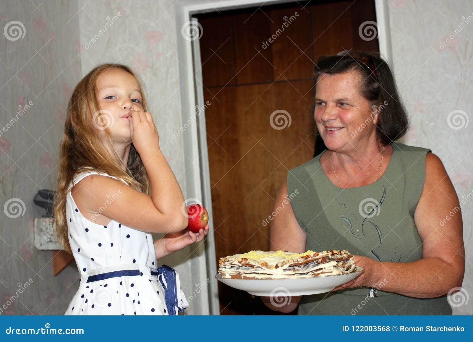 Une petite fille goûte un gâteau par sa main du plat
