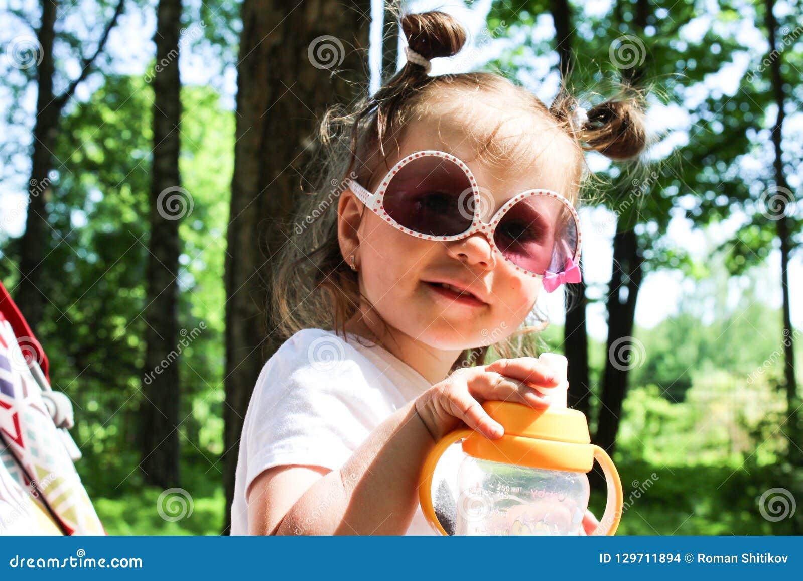 Une petite fille marche se reposer dans un landau dans des lunettes de soleil