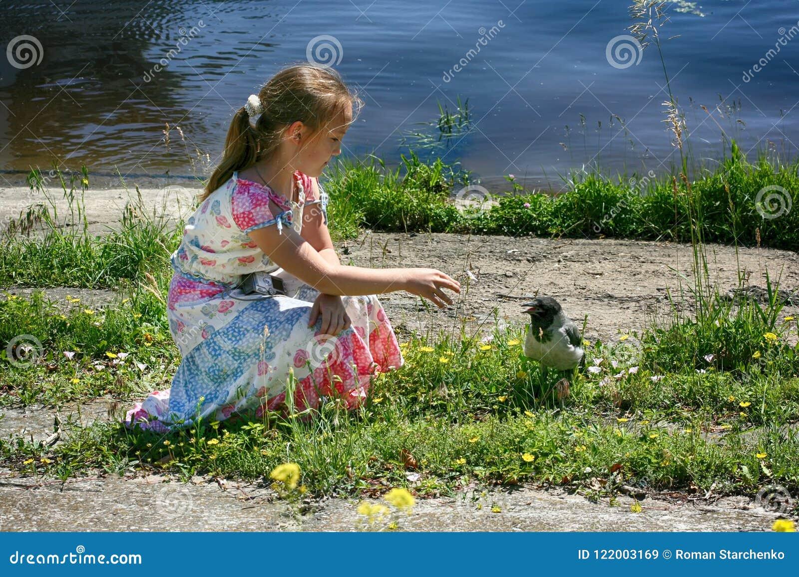 Une petite fille s assied par l eau et atteint à une petite corneille
