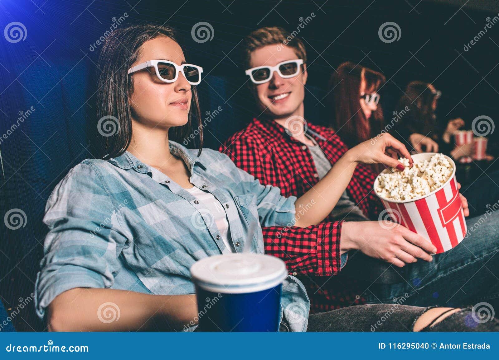 Une photo de société se reposant ensemble dans une rangée dans le hall de cinéma La fille observe le film dans les verres et l at