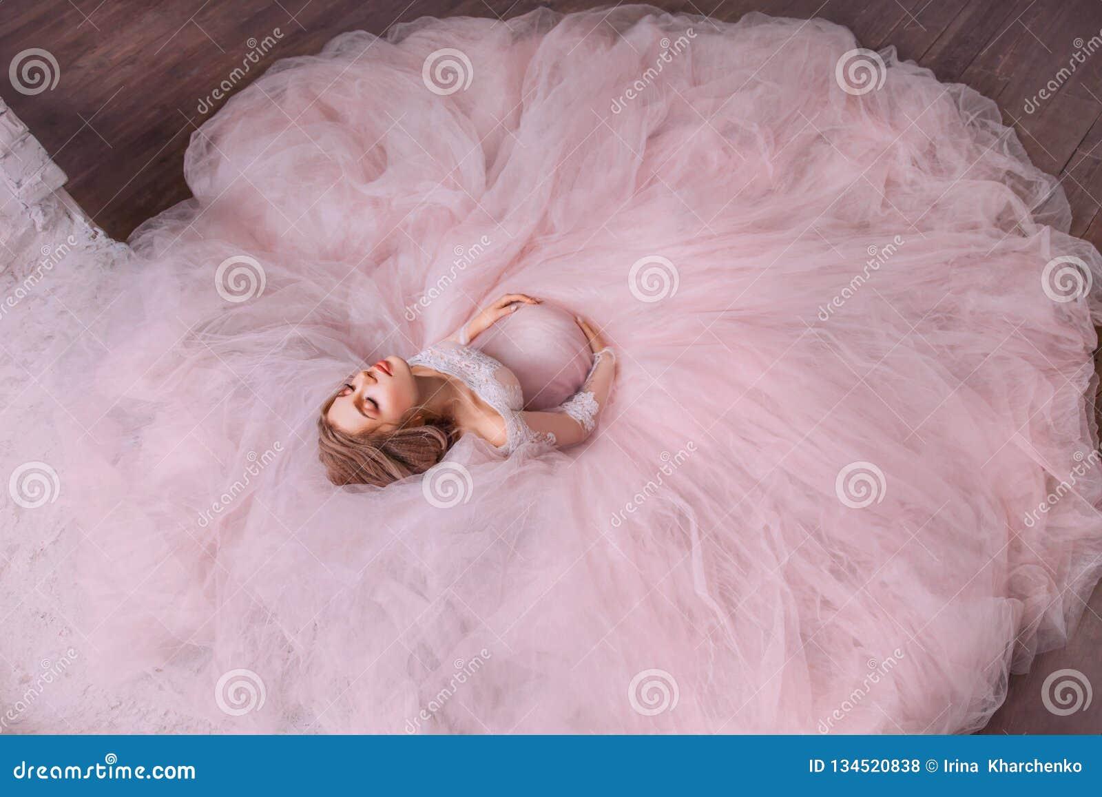 Une photo magique fabuleuse d une jolie fille enceinte attirante avec les cheveux blonds dans une robe rose magnifique magnifique