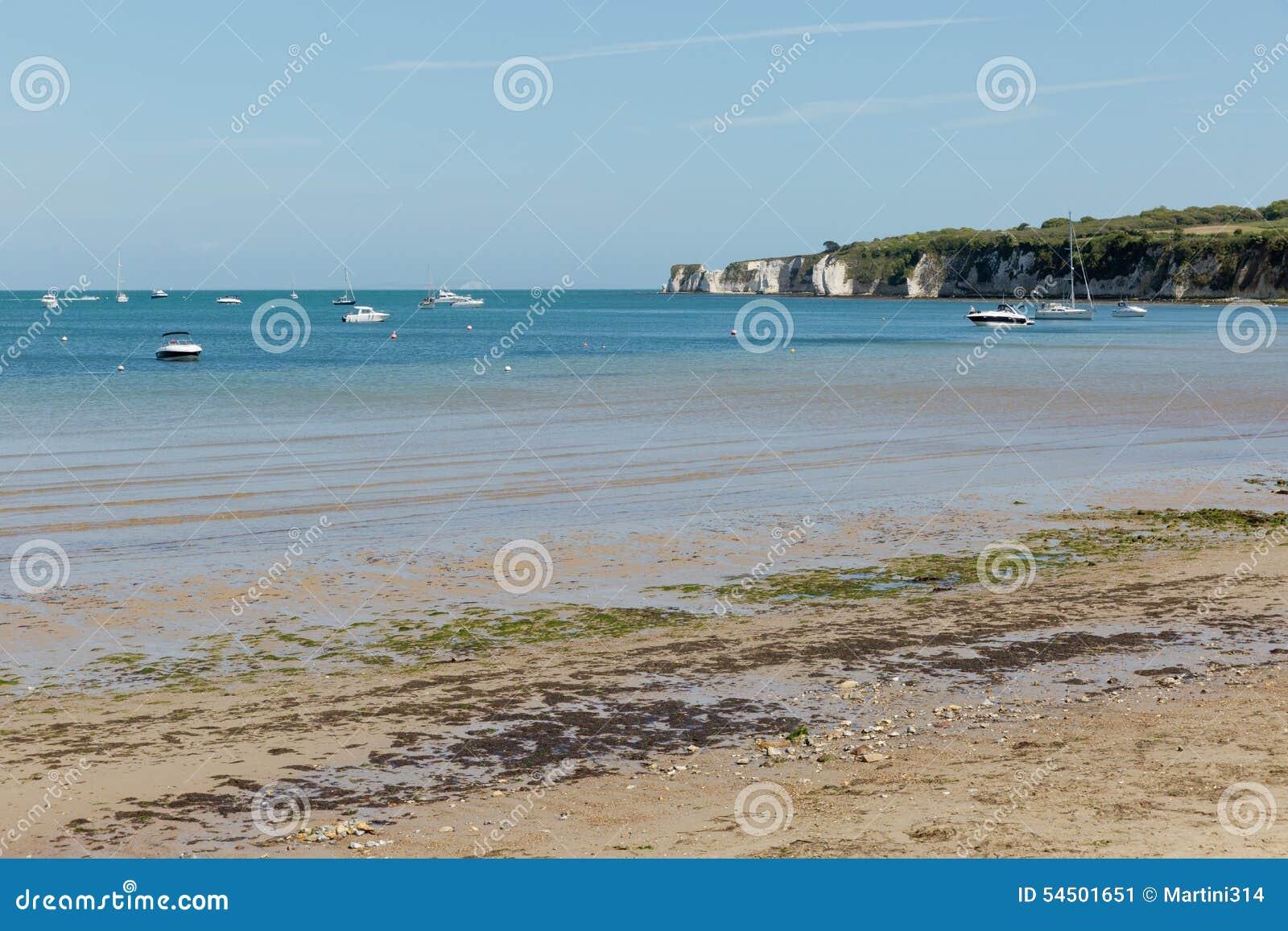Une photo prise une journée de printemps à la plage de Swanage regardant vers les bateaux sur la mer et la côte jurasic rayent