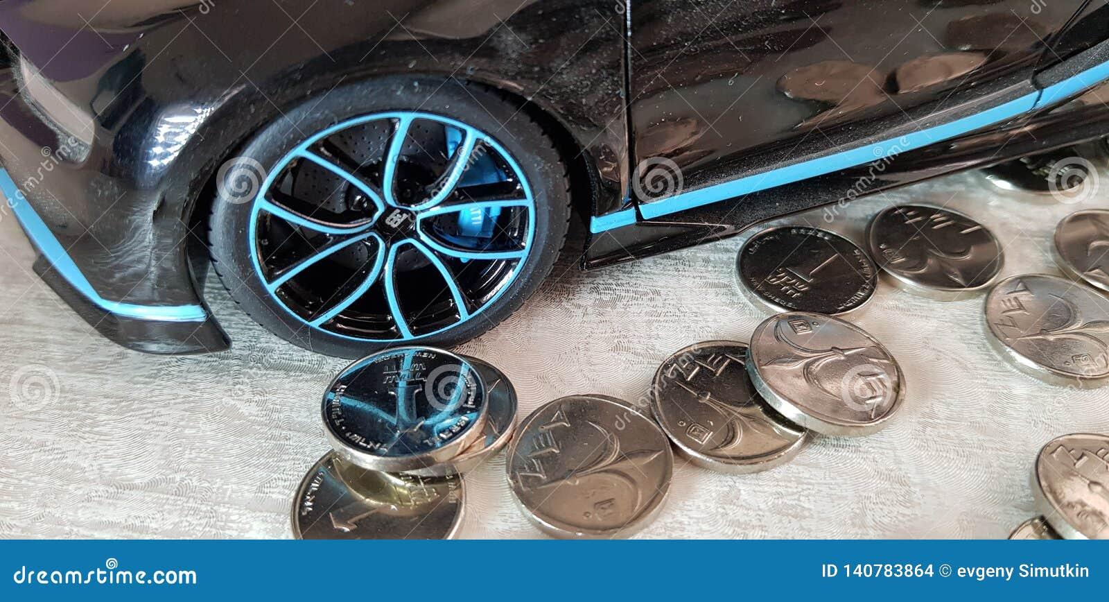 Une pièce de monnaie israélienne de shekel près de jouet en métal de noir de Bugatti Chiron avec la réflexion d argent de la roue