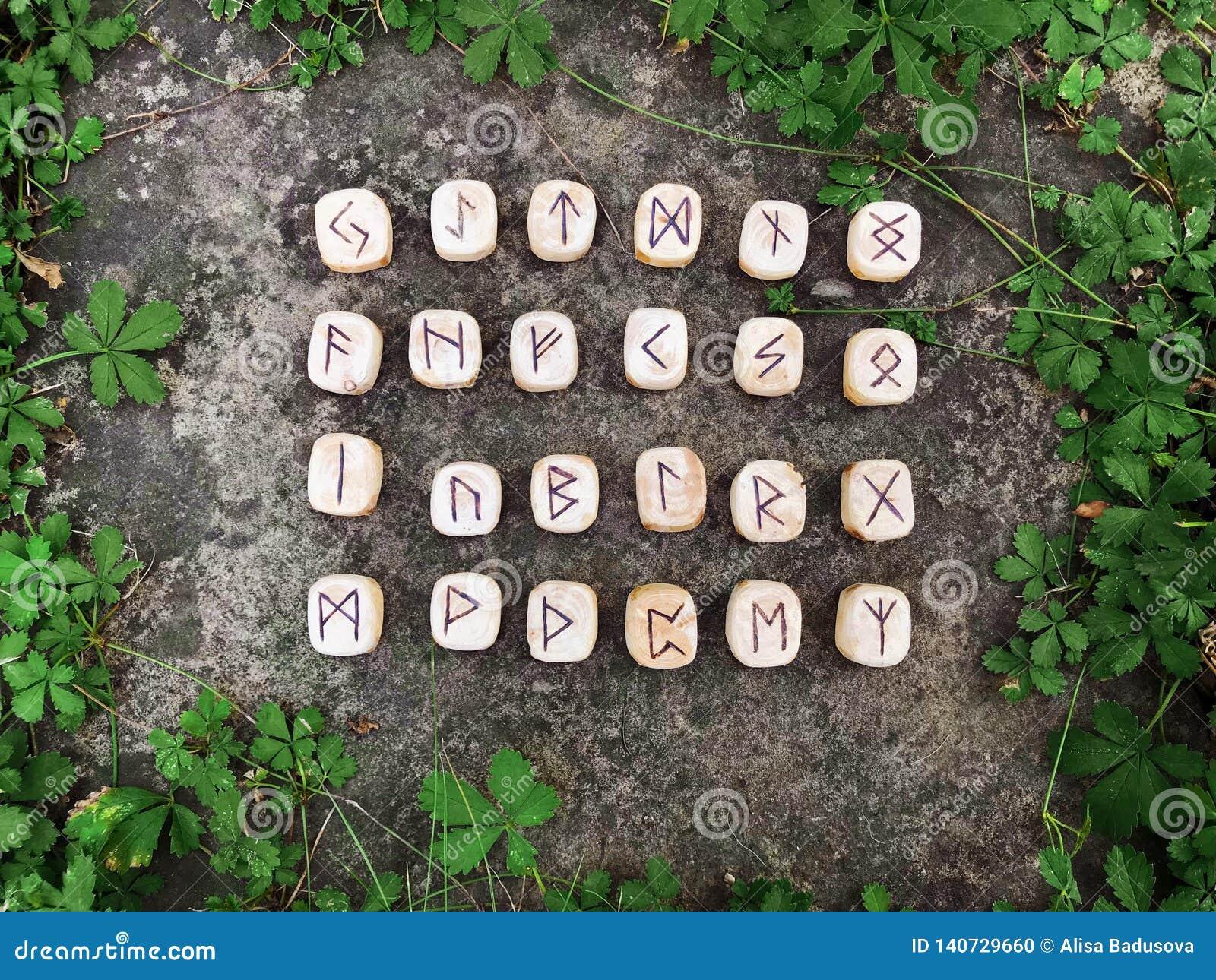 Une pile de runes en bois aux runes en bois de forêt se trouvent sur un fond de roche dans l herbe verte Des runes sont coupées d