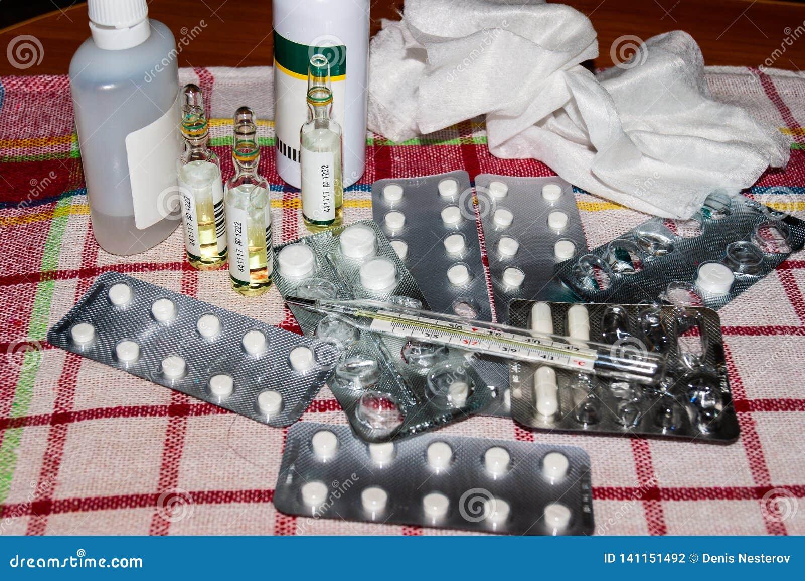 Une pile des pilules, des drogues et d un thermomètre sur une serviette
