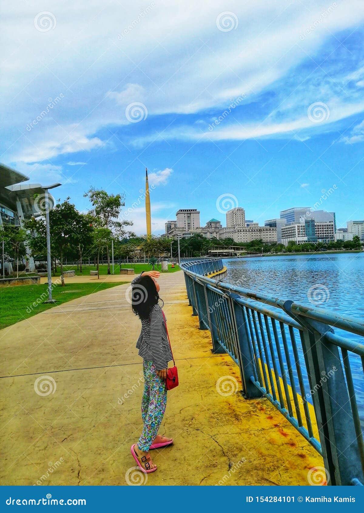 Une position malaise de fille au lac, regardant les cieux nuageux chez Precint 8, Putrajaya Malaisie