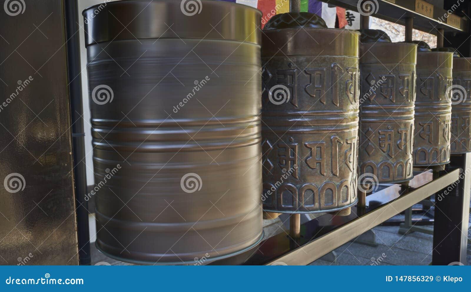 Une rangée des roues de prière bouddhistes, l une d entre elles tourne