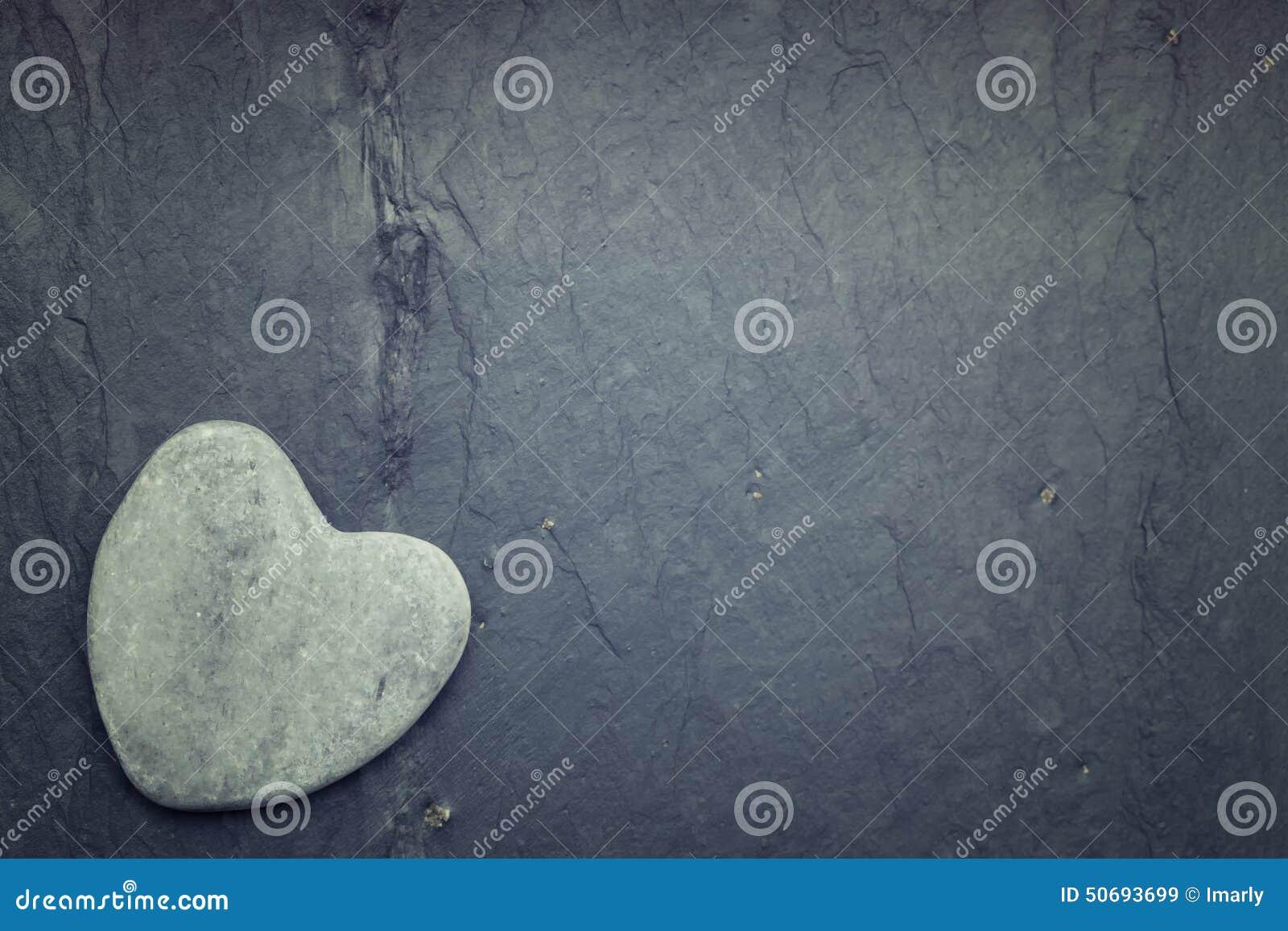 Une roche en forme de coeur de zen gris dans le coin sur un fond de tuile