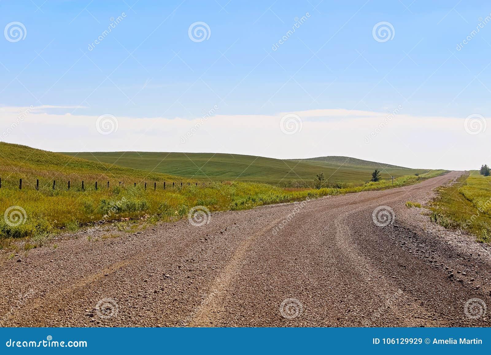 Une route de gravier par des terres cultivables et des collines d Alberta