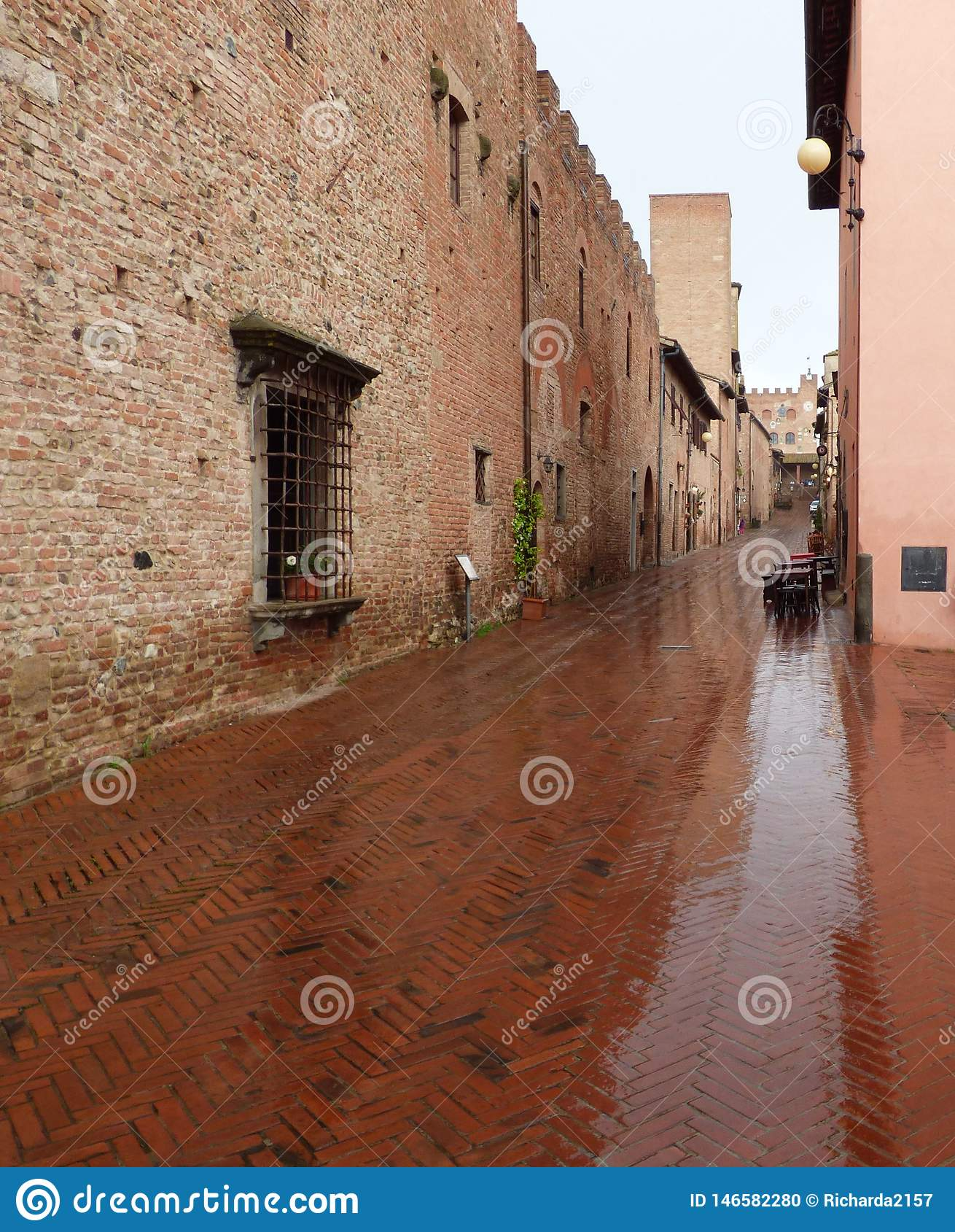 Une rue humide de brique dans Certaldo Italie