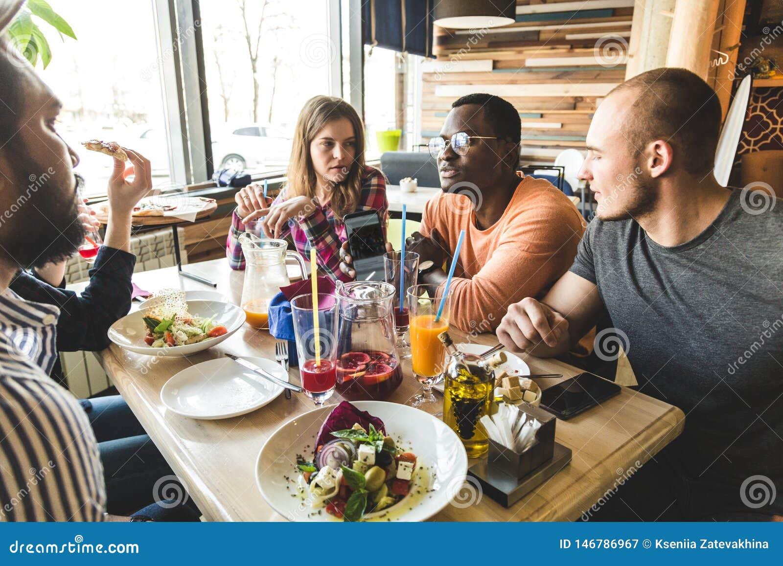 Une soci?t? des jeunes multiculturels dans un caf? mangeant de la pizza, cocktails potables, ayant l amusement
