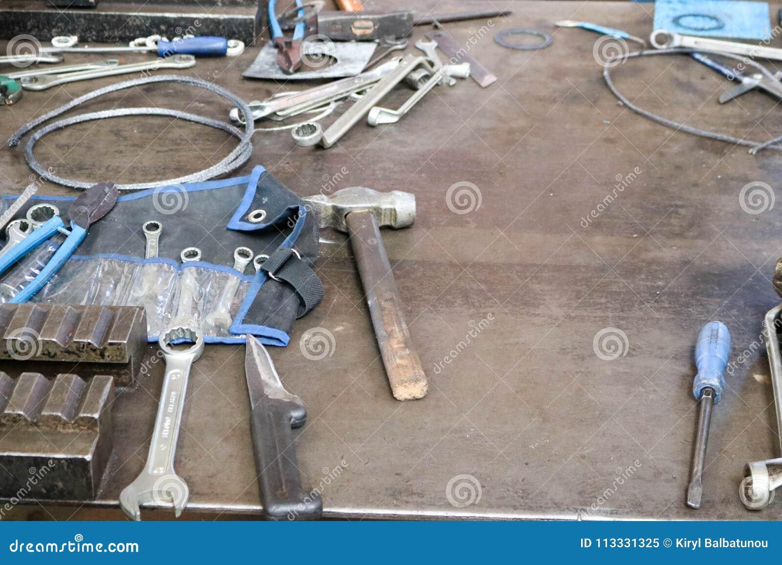 Une table de fer avec un outil de métal ouvré, clés, marteaux, tournevis, coupe-fil, couteaux, fil dans l usine, une usine