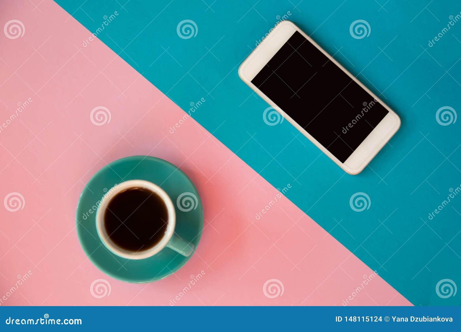 Une tasse bleue avec du café et un téléphone portable se tient sur un rose et un fond bleu Petit d?jeuner de matin, affaires