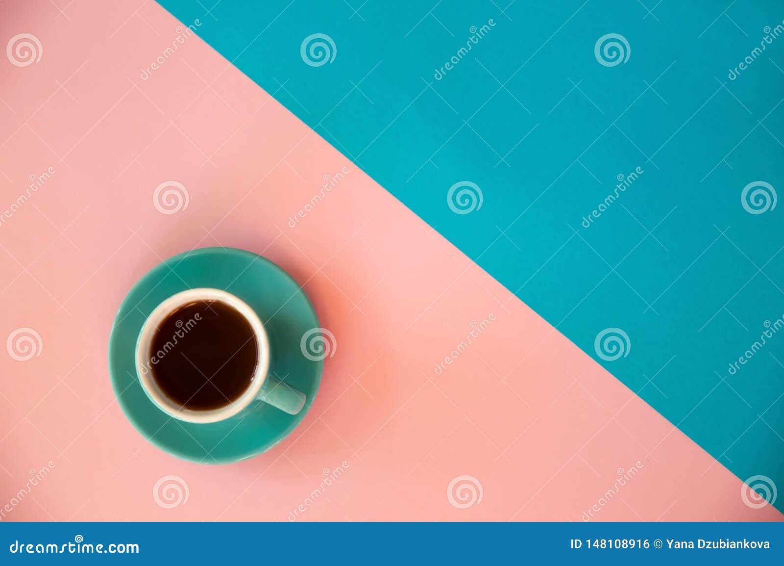 Une tasse bleue de supports de café sur un rose et un fond bleu Petit d?jeuner de matin, affaires