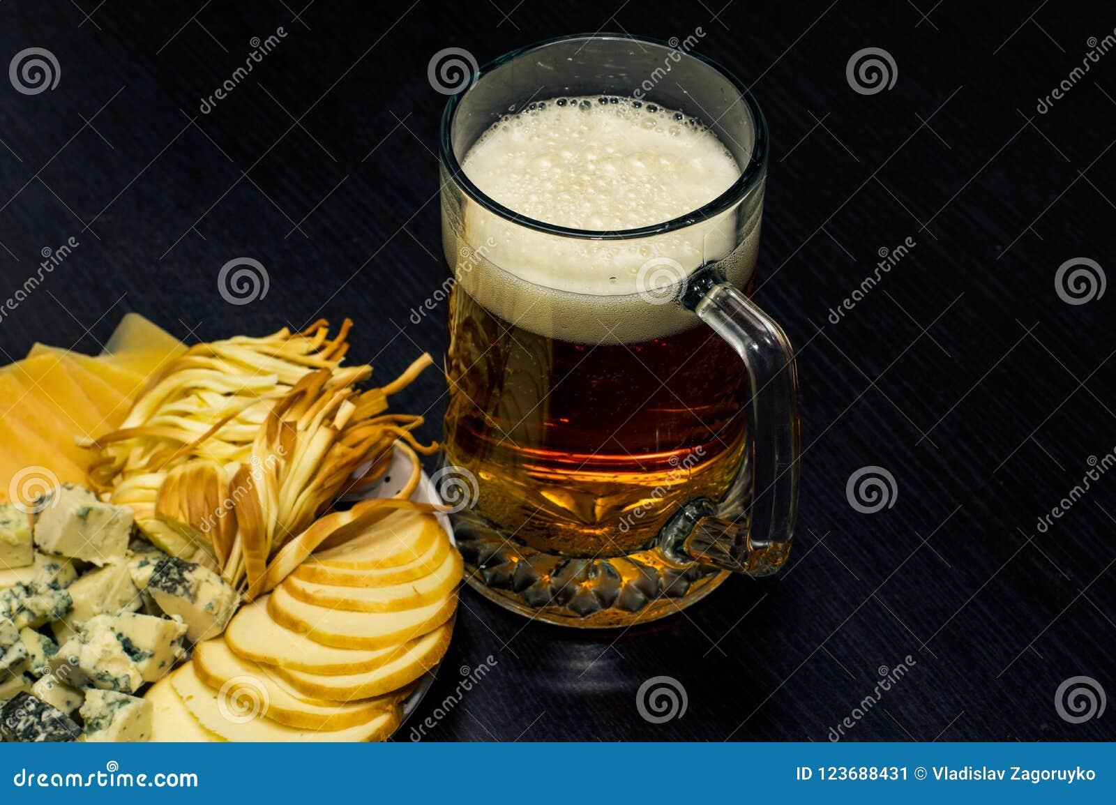Une tasse de bière et un plat avec plusieurs genres de fromage