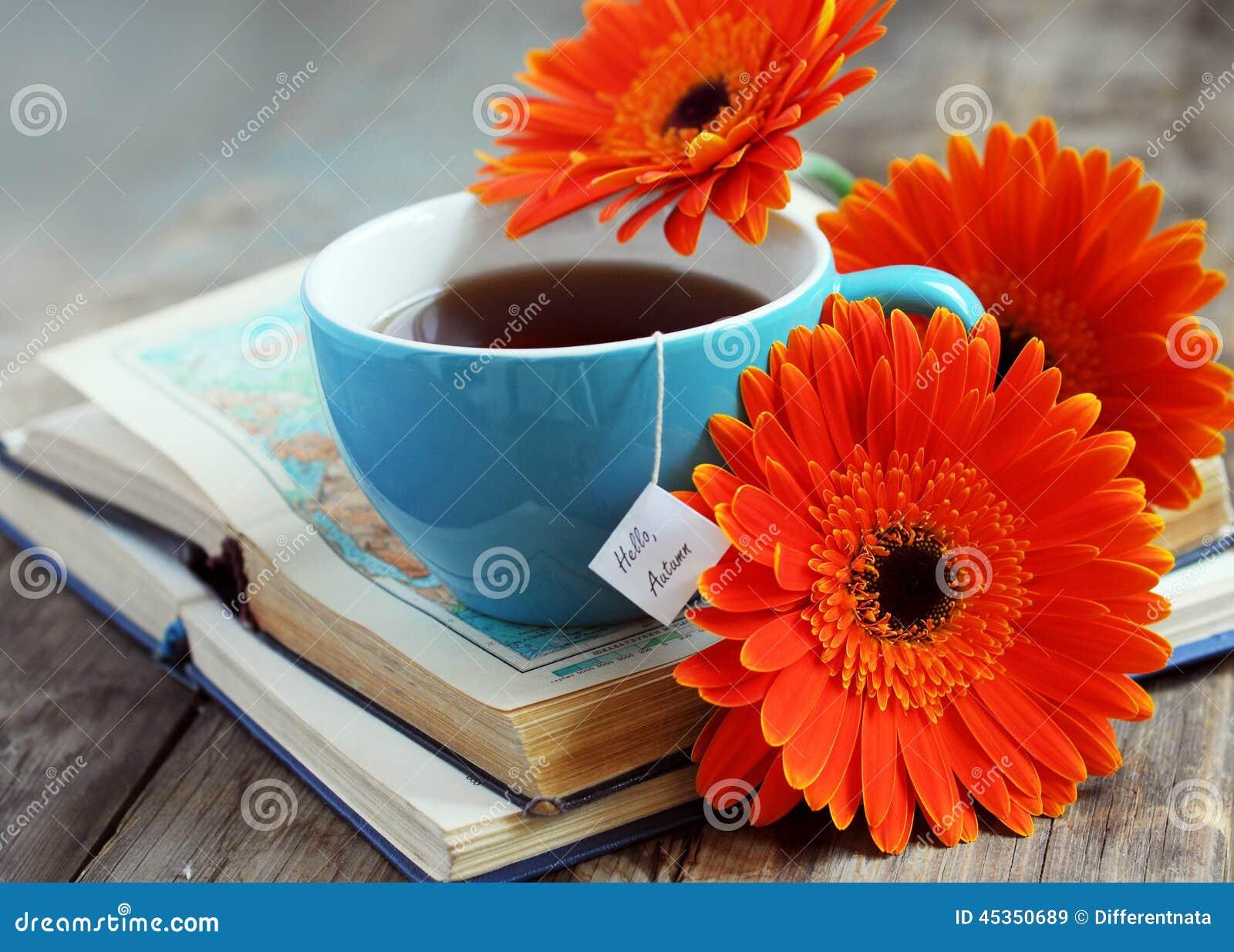 Une tasse de thé avec des fleurs et des livres de gerbera
