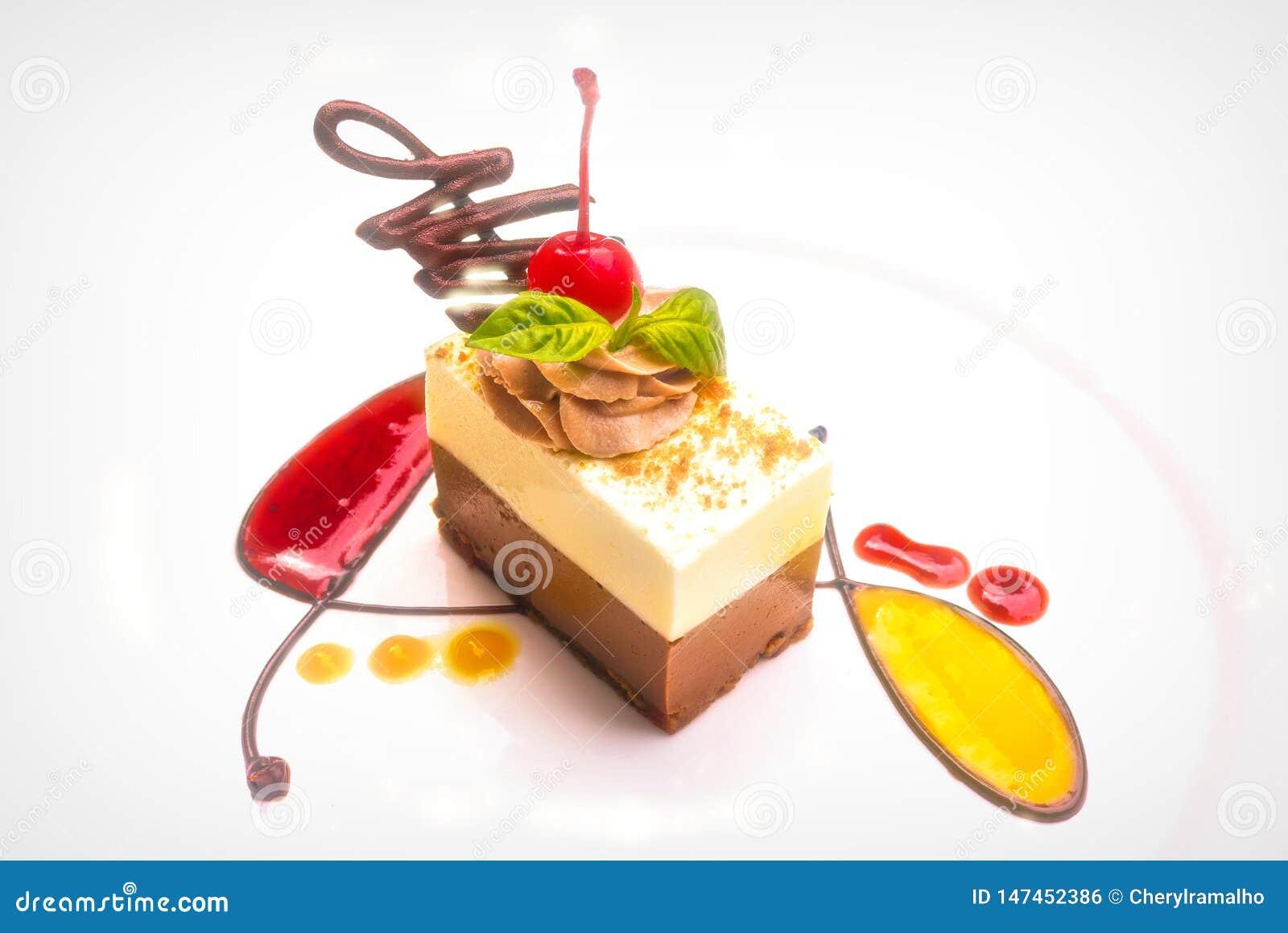 Une tranche délicieuse et belle de torte blanc et foncé de chocolat avec le coulis de fruit frais