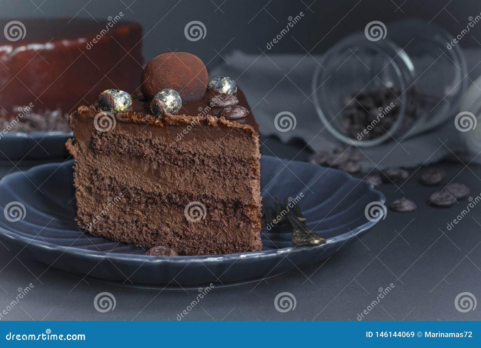 Une tranche de gâteau de  brownie  de chocolat, dessert avec des écrous sur le fond foncé