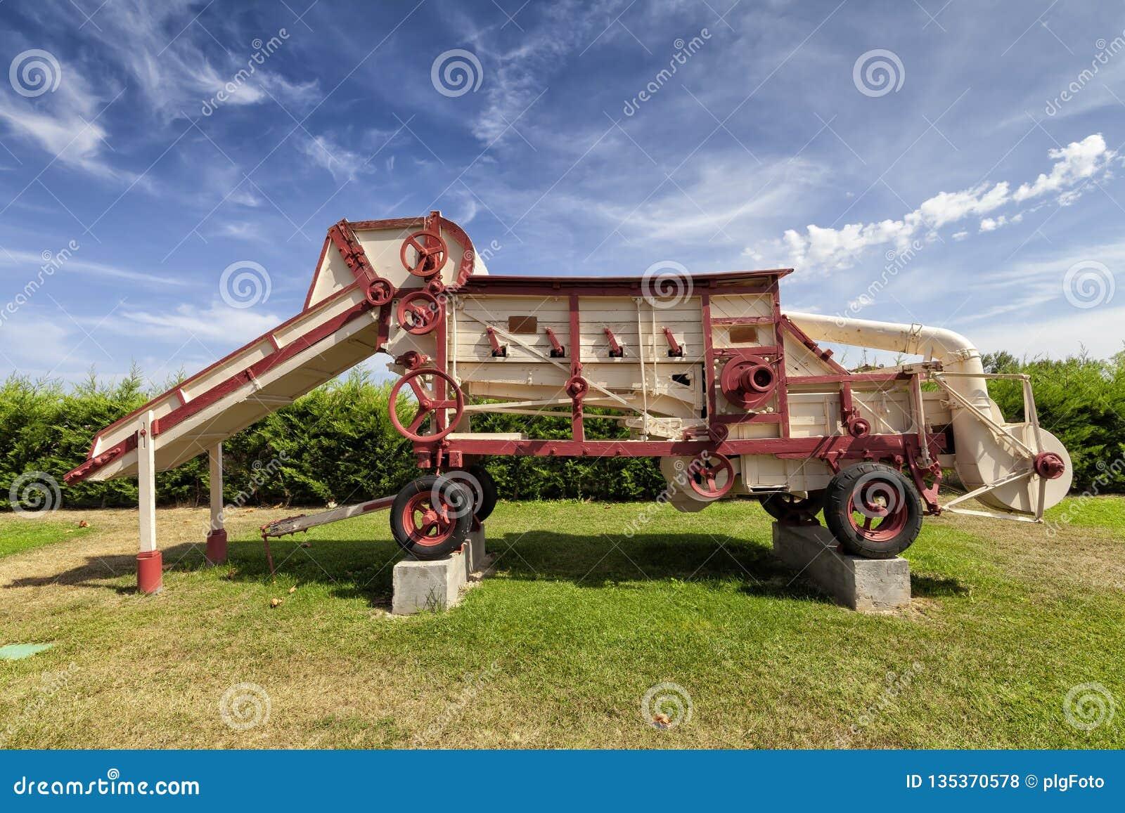 Une vieille batteuse de grain utilisée comme monument