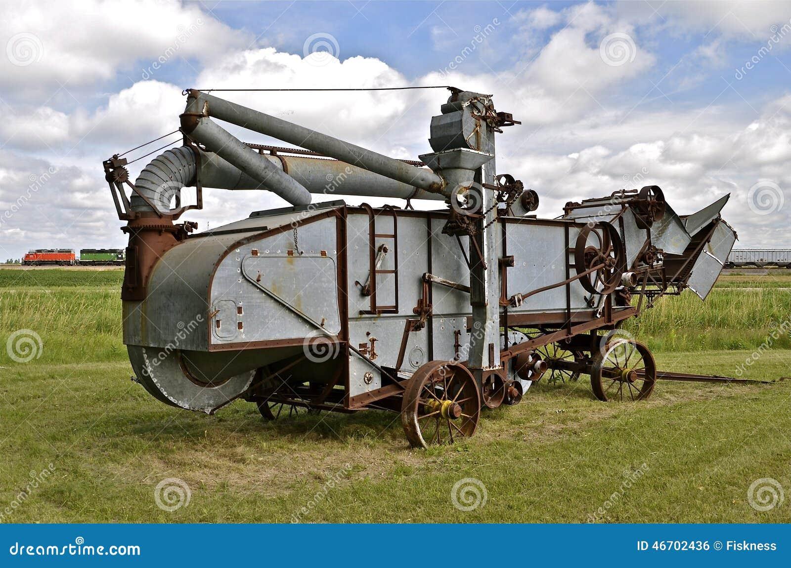 Une vieille batteuse réside dans un domaine avec un train de fret passant à l arrière-plan